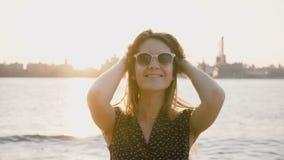 Πορτρέτο του νέου όμορφου flirty ευρωπαϊκού κοριτσιού στα γυαλιά ηλίου που χαμογελά στη κάμερα στο ηλιοβασίλεμα ποταμών πόλεων τη φιλμ μικρού μήκους