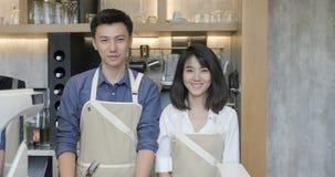 Πορτρέτο του νέων ασιατικών άνδρα και της γυναίκας barista δύο που διασχίζουν τα χέρια και που χαμογελούν στη κάμερα στον καφέ κα φιλμ μικρού μήκους