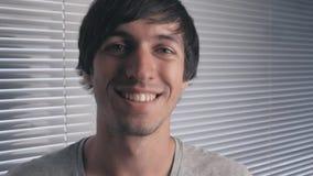 Πορτρέτο του νεαρού άνδρα με το μακρυμάλλες χαμόγελο στο υπόβαθρο των τυφλών γραφείων απόθεμα βίντεο