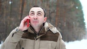 Πορτρέτο του νεαρού άνδρα που μιλά στο τηλέφωνο στο χειμερινό δάσος απόθεμα βίντεο