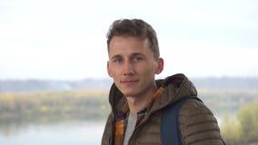 Πορτρέτο του νεαρού άνδρα υπαίθρια με το πολύ όμορφο πρόσωπο στο περιστασιακό σακάκι και το πουκάμισο στο φυσικό κλίμα απόθεμα βίντεο