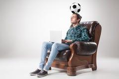 Πορτρέτο του νεαρού άνδρα με το lap-top και τη σφαίρα ποδοσφαίρου Στοκ Εικόνες