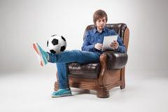 Πορτρέτο του νεαρού άνδρα με το lap-top και τη σφαίρα ποδοσφαίρου Στοκ Εικόνα