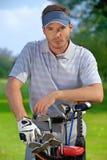 Πορτρέτο του νεαρού άνδρα που υπερασπίζεται το σύνολο τσαντών γκολφ των ραβδιών Στοκ εικόνα με δικαίωμα ελεύθερης χρήσης