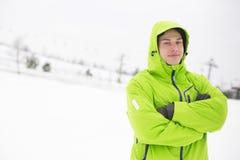 Πορτρέτο του νεαρού άνδρα στα με κουκούλα μόνιμα όπλα σακακιών που διασχίζονται στο χιόνι Στοκ Εικόνες