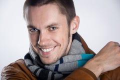 Πορτρέτο του νεαρού άνδρα στο καφετί σακάκι με το ριγωτό μαντίλι πέρα από το γκρίζο υπόβαθρο. Κινηματογράφηση σε πρώτο πλάνο. στοκ εικόνα