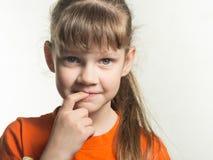 Πορτρέτο του ντροπαλού κοριτσιού με το δάχτυλο στο στόμα στο άσπρο υπόβαθρο στοκ φωτογραφία με δικαίωμα ελεύθερης χρήσης