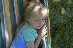 Πορτρέτο του ξανθού κοριτσιού παιδιών, που χαλαρώνει σε μια ζωηρόχρωμη αιώρα Στοκ Εικόνα