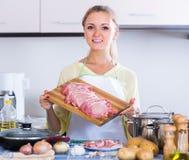 Πορτρέτο του ξανθού κοριτσιού που προετοιμάζει το κρέας στο εσωτερικό Στοκ εικόνα με δικαίωμα ελεύθερης χρήσης