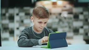 Πορτρέτο του ξανθού νέου παιχνιδιού αγοριών παιδιών με έναν ψηφιακό υπολογιστή ταμπλετών, μουσική ακούσματος με τα ακουστικά απόθεμα βίντεο