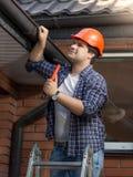 Πορτρέτο του ξυλουργού hardhat που εξετάζει τη στέγη σπιτιών Στοκ Εικόνες