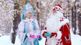 Πορτρέτο του παγετού πατέρων και του χαμογελώντας κοριτσιού χιονιού που παρουσιάζουν δώρα στη κάμερα φιλμ μικρού μήκους