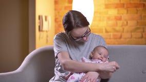 Πορτρέτο του παιχνιδιού μητέρων με τη χαριτωμένη νεογέννητη κόρη της που προσέχει smilingly στη κάμερα στο καθιστικό απόθεμα βίντεο