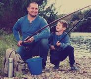 Πορτρέτο του πατέρα και του γιου που αλιεύουν με τις ράβδους στοκ εικόνα