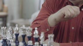 Πορτρέτο του παχουλού ατόμου στο κόκκινο πουκάμισο που σκέφτεται σκληρά πριν για να γίνει μια κίνηση με το κομμάτι σκακιού Καυκάσ απόθεμα βίντεο