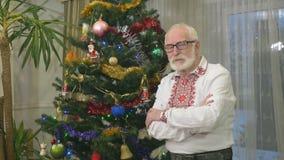 Πορτρέτο του παλαιού παππού κοντά στο χριστουγεννιάτικο δέντρο φιλμ μικρού μήκους