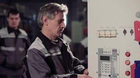 Πορτρέτο του πεπειραμένου εργαζομένου που ανοίγει έναν ηλεκτρικό μετρητή απόθεμα βίντεο