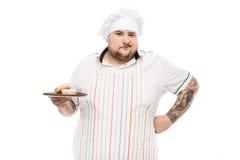 Πορτρέτο του πιάτου εκμετάλλευσης αρχιμαγείρων μορφασμού με doughnuts Στοκ Φωτογραφίες