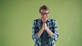 Πορτρέτο του πονηρού νεαρού άνδρα που τρίβει τα χέρια του και που χαμογελά την εξέταση τη κάμερα απόθεμα βίντεο