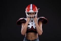 Πορτρέτο του προκλητικού ελκυστικού νέου κοριτσιού με μια φωτεινή σύνθεση σε μια αθλητική εξάρτηση για το αμερικανικό ποδόσφαιρο στοκ εικόνες