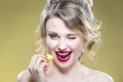 Πορτρέτο του προκλητικού καυκάσιου ξανθού κοριτσιού που τρώει το μικροσκοπικό κομμάτι λεμονιών