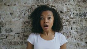 Πορτρέτο του σγουρού κοριτσιού εφήβων αφροαμερικάνων ενεργά που εκπλήσσει και που αναρωτιέται στο υπόβαθρο τουβλότοιχος απόθεμα βίντεο