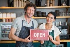Πορτρέτο του σερβιτόρου και της σερβιτόρας που κρατούν την ανοικτή πινακίδα Στοκ Φωτογραφία