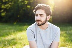 Πορτρέτο του σκεπτικού γενειοφόρου αρσενικού με το μοντέρνο hairdo που κοιτάζει κάτω με τα γοητευτικά μεγάλα σκοτεινά μάτια του π Στοκ Εικόνες
