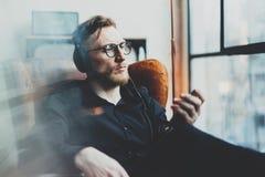 Πορτρέτο του σκεπτικού γενειοφόρου ατόμου που φορά τα γυαλιά, τα ακουστικά και το άκουσμα στη μουσική στο σύγχρονο σπίτι Συνεδρία Στοκ εικόνα με δικαίωμα ελεύθερης χρήσης