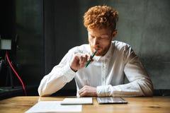 Πορτρέτο του σκεπτόμενου νέου ατόμου readhead στο άσπρο πουκάμισο, κάθισμα Στοκ φωτογραφία με δικαίωμα ελεύθερης χρήσης