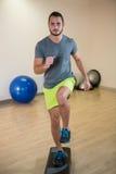 Πορτρέτο του σοβαρού ατόμου που κάνει την άσκηση αεροβικό stepper στοκ φωτογραφία με δικαίωμα ελεύθερης χρήσης