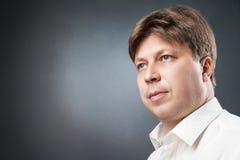 Πορτρέτο του σοβαρού ατόμου στο μαύρο κλίμα Στοκ Εικόνες