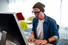 Πορτρέτο του σοβαρού ατόμου hipster που εργάζεται στο γραφείο υπολογιστών Στοκ Εικόνα