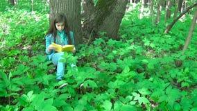 Πορτρέτο του σοβαρού βιβλίου ανάγνωσης έφηβη και της γυρίζοντας σελίδας που κλίνουν ενάντια στον κορμό δέντρων στο δάσος την άνοι απόθεμα βίντεο