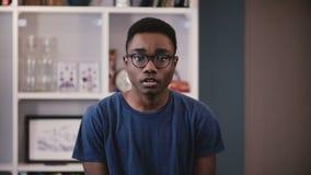 Πορτρέτο του σοβαρού σπουδαστή αφροαμερικάνων Όμορφα στοχαστικά μαύρα γυαλιά ρύθμισης νεαρών άνδρων που εξετάζουν τη κάμερα 4K απόθεμα βίντεο
