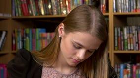 Πορτρέτο του σπουδαστή σε μια βιβλιοθήκη όμορφο θηλυκό απόθεμα βίντεο