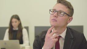 Πορτρέτο του στοχαστικού νεαρού άνδρα στα γυαλιά που κάθεται στο πρώτο πλάνο στο γραφείο ενώ η γυναίκα συνάδελφός του σε επίσημο απόθεμα βίντεο