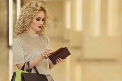 Πορτρέτο του στοχαστικού όμορφου προσώπου που κρατά το ανοικτό πορτοφόλι με τη σκεπτική έκφραση στο εμπορικό κέντρο με τα καταστή στοκ φωτογραφία