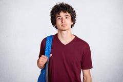 Πορτρέτο του στοχαστικού όμορφου τύπου με τη σγουρή μαύρη τρίχα που στέκεται κατ' ευθείαν, έχοντας το μπλε σακίδιο πλάτης στην πλ στοκ εικόνα με δικαίωμα ελεύθερης χρήσης