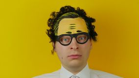 Πορτρέτο του συγκλονισμένου και έκπληκτου σγουρού ατόμου, αστείος και χαρωπά της συγκίνησης, στο κίτρινο υπόβαθρο τοίχων απόθεμα βίντεο