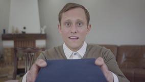 Πορτρέτο του συγκρατημένα ντυμένου ατόμου που κρατά tremblingly το βιβλίο, που εξετάζει τη κάμερα Αστείο ξανθό άτομο που αγαπά απόθεμα βίντεο