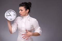 Πορτρέτο του συμπαθητικού κοριτσιού που κρατά το μεγάλο ρολόι σε την Στοκ εικόνες με δικαίωμα ελεύθερης χρήσης