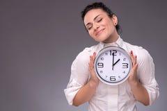 Πορτρέτο του συμπαθητικού κοριτσιού που κρατά το μεγάλο ρολόι σε την Στοκ Εικόνα