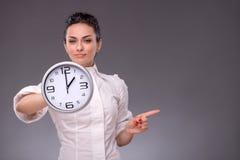 Πορτρέτο του συμπαθητικού κοριτσιού που κρατά το μεγάλο ρολόι σε την Στοκ Φωτογραφία