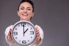 Πορτρέτο του συμπαθητικού κοριτσιού που κρατά το μεγάλο ρολόι σε την Στοκ Εικόνες