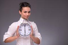 Πορτρέτο του συμπαθητικού κοριτσιού που κρατά το μεγάλο ρολόι σε την Στοκ Φωτογραφίες
