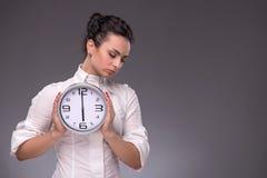 Πορτρέτο του συμπαθητικού κοριτσιού που κρατά το μεγάλο ρολόι σε την Στοκ φωτογραφία με δικαίωμα ελεύθερης χρήσης