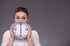 Πορτρέτο του συμπαθητικού κοριτσιού που κρατά το μεγάλο ρολόι σε την Στοκ φωτογραφίες με δικαίωμα ελεύθερης χρήσης