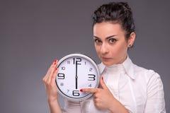 Πορτρέτο του συμπαθητικού κοριτσιού που κρατά το μεγάλο ρολόι Στοκ Εικόνες