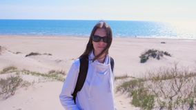 Πορτρέτο του ταξιδιώτη νέων κοριτσιών με το σακίδιο πλάτης στην παραλία άμμου θάλασσας στις διακοπές φιλμ μικρού μήκους
